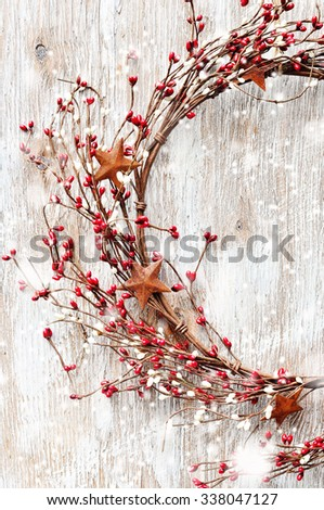 Christmas wreath with red and white berries and rusty metal stars on wooden background. Falling snow effect. Copy space. Vintage Style - stock photo