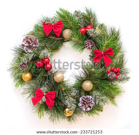 Christmas wreath with red bows, cones, balls and berries. - stock photo