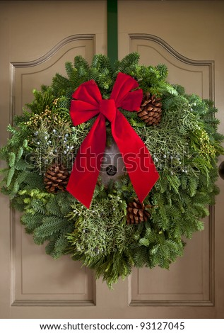 Christmas wreath with red ribbon handing on classic door front. - stock photo