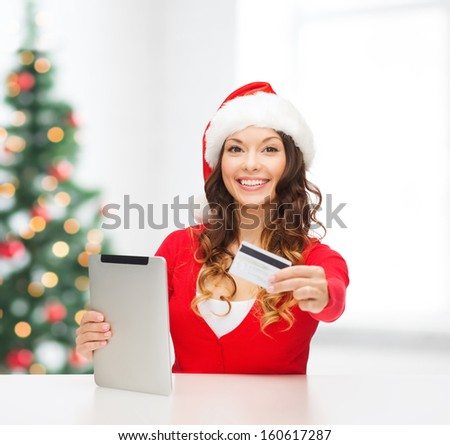 christmas, x-mas, online shopping concept - woman in santa helper hat with gift box, tablet pc computer and credit card - stock photo