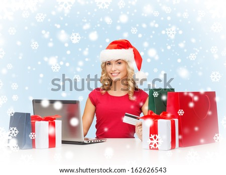 christmas, x-mas, online shopping concept - woman in santa helper hat with gift boxes, bags, laptop computer and credit card - stock photo