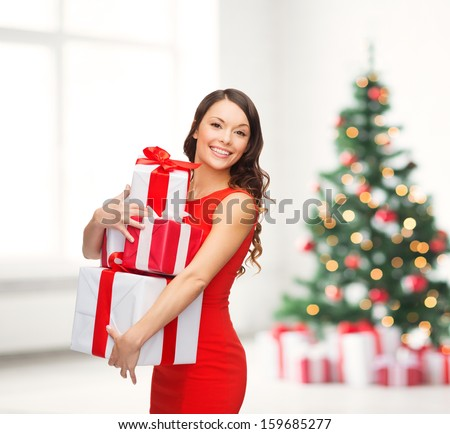 christmas, x-mas, valentine's day, celebration concept - smiling woman in red dress with many gift boxes - stock photo