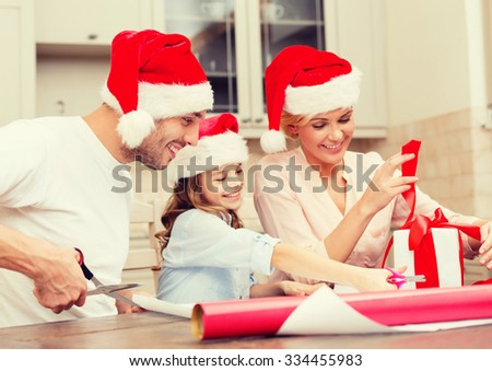 christmas, x-mas, winter,family, happiness and people concept - smiling family in santa helper hats with gift box - stock photo