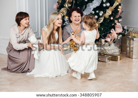 christmas, x-mas, winter, happiness concept - smiling happy family: grandmother, mother, daughter, granddaughter gift near the Christmas tree, 4 generations of the family, four, love concept - stock photo