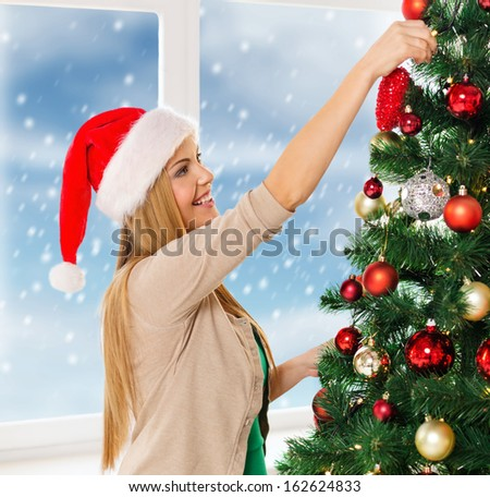 christmas, x-mas, winter, happiness concept - smiling woman in santa helper hat decorating a christmas tree - stock photo