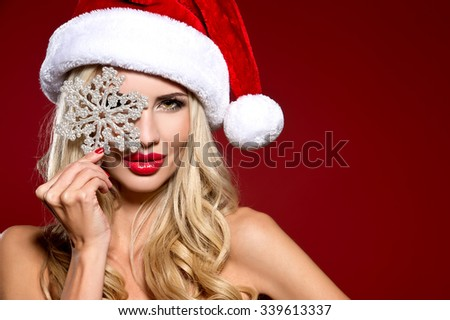 christmas, x-mas, winter, happiness concept - smiling woman in santa helper hat with many gift boxes. picture of cheerful santa helper girl with snowflake - stock photo
