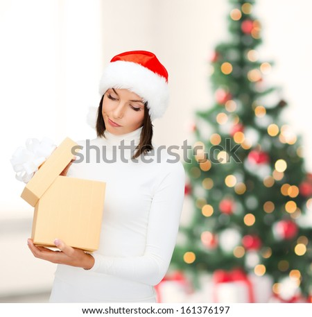 christmas, x-mas, winter, happiness concept - suspicious woman in santa helper hat with gift box - stock photo