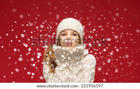 christmas, xmas and happiness concept - happy girl in winter clothes blowing on palms - stock photo