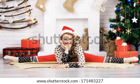 Christmas yoga. Lovely girl doing yoga exercise at home. - stock photo