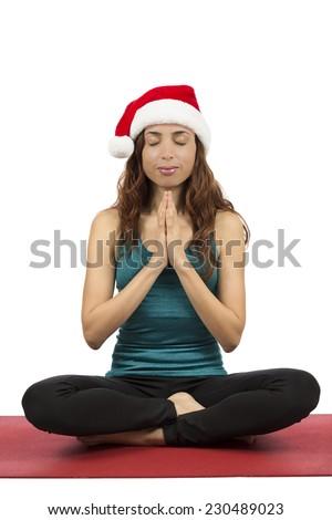 Christmas yoga woman with santa hat in meditation - stock photo