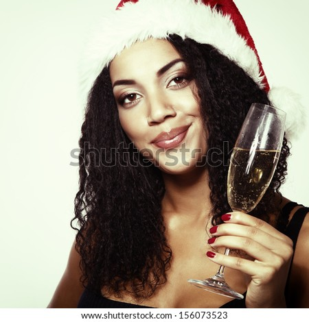 christmas young beautiful mulatto woman smiling with champagne and in santa's hat - stock photo