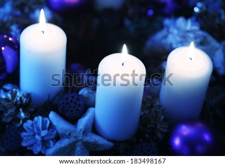 Chritmas candles on decorated wreath - stock photo