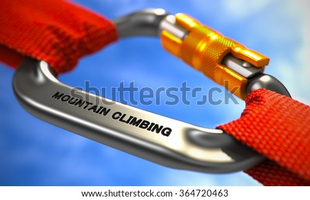 Chrome Carabiner between Red Ropes on Sky Background, Symbolizing the Mountain Climbing. Selective Focus. - stock photo