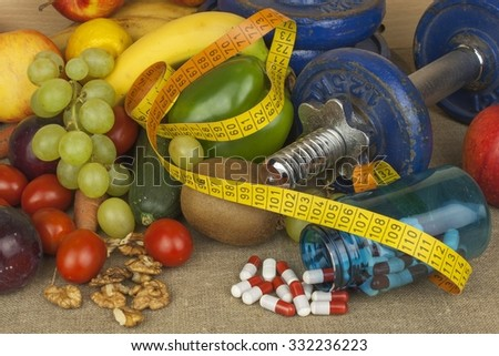 Chrome dumbbells surrounded with healthy fruits and vegetables on a table. Concept of healthy eating and weight loss. Diet for athletes. Muscle building. - stock photo