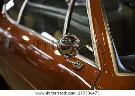 Chrome rear view mirror of a red car - stock photo