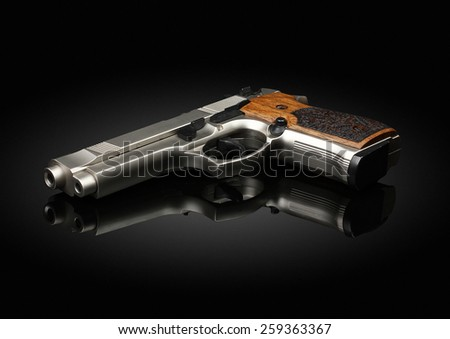 Chromed handgun on black background with reflection - stock photo
