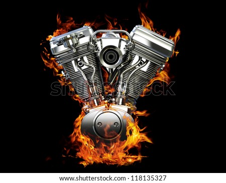 Chromed motorcycle engine on fire on a black background - stock photo