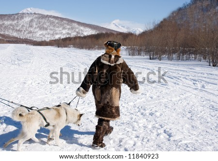 chukchi in national gown leads harness with dog - stock photo