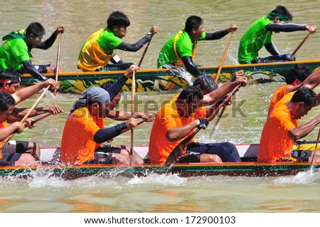 CHUMPHON, THAILAND - OCT 21: Boaters paddle in Row boat racing on October 21, 2013 in Lang Suan, Chumphon, Thailand. Highlight is flag racing  at finish line. - stock photo