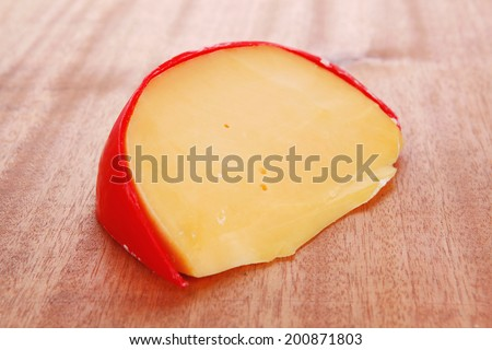 chunk of aged french cheddar cheese in hard red shell on wooden table - stock photo