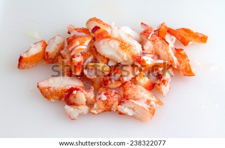 Chunks of cooked cut lobster meat on a plastic white cutting board. - stock photo