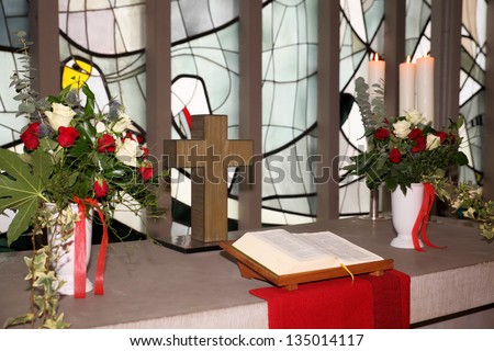Church altar with cross, flowers and bible - stock photo