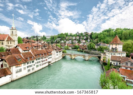 Church, bridge and houses with tiled rooftops, Bern, Switzerland - stock photo