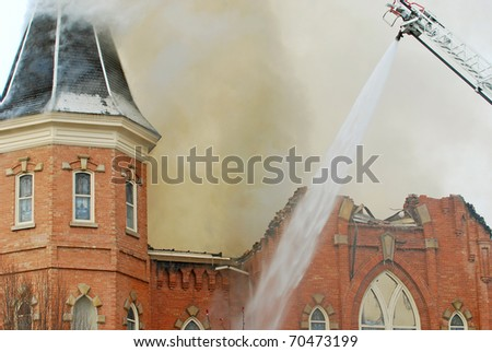 Church building on fire with firefighters spraying water on the walls from a ladder. - stock photo