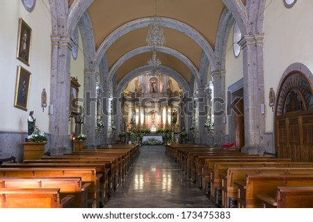 Church interior in Chapala Mexico with columns and arches forming nave and illuminated altar - stock photo
