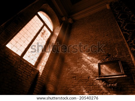 Church interior: window and light beams on wall, red toned - stock photo