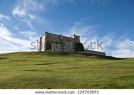 Church of San Martin de Atapuerca, in Burgos, Spain, on top of a hill with a blue background - stock photo