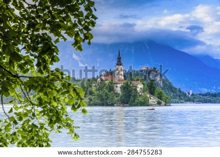Church of the Assumption in Lake Bled with the castle in the background, Slovenia - stock photo