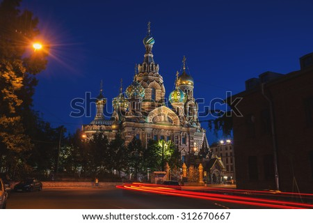 Church of the Savior on Spilled Blood at night - famous landmark in Saint Petersburg, Russia. Illuminated building with dark clear blue sky at the background. Car light trails  - stock photo