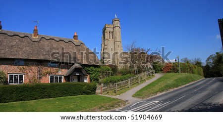 Church on a hill and thatched cottages, two iconic elements of a traditional English village - stock photo