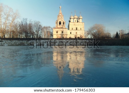 Church on the banks of the frozen river ice winter - stock photo