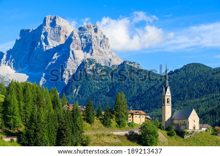 Church on top of hill in village of Pian near Selva di Cadore and beautiful mountains view, South Tirol, Dolomiti Mountains, Italy  - stock photo