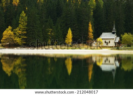 Church Reflection on Lago di Braies, Dolomites, Italy - stock photo