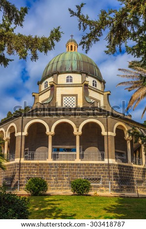 Church Sermon on the Mount - Mount of Beatitudes. The basilica is surrounded by a gallery with columns. Subtle shade of palms and cypresses - stock photo