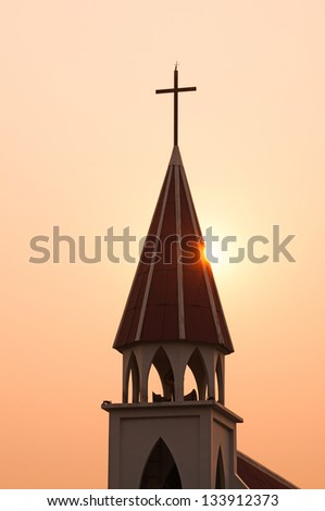 Church steeple silhouette at sunset - stock photo