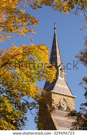church steeple with fall leaves - stock photo