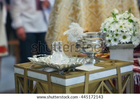 Church supplies for baptism on the table. Ceremony of a christening in church. - stock photo