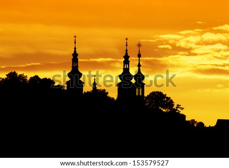 Church towers silhouettes in Prague at sunset. - stock photo