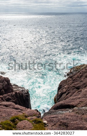 Churning water and waves splashing on steep rocky red coastal inlet against ocean under overcast sky, in Newfoundland, Canada. - stock photo