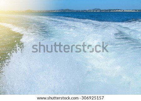 Churning water in the wake of departing boat - stock photo