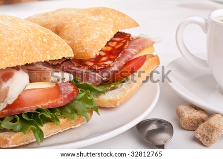 Ciabatta bread sandwich stuffed meat,cheese and vegetables with cup of coffee - stock photo