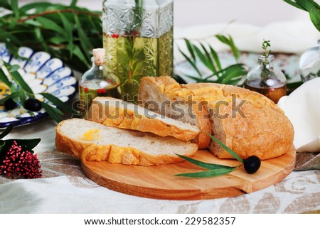 Ciabatta in still life on blackboard with olives and olive oil in the Italian style - stock photo
