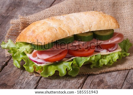 ciabatta sandwich with ham and vegetables on an old wooden table. horizontal  - stock photo