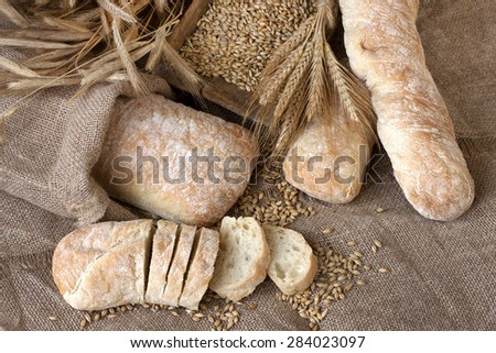 Ciabatta with ears on the wooden table - stock photo