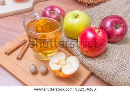 Cider - alcohol hot apple drink and apples on wooden table - stock photo