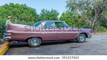 CIENFUEGOS, CUBA - MARCH 23, 2012: Rural road parking with Dodge Kingsway sedan - stock photo